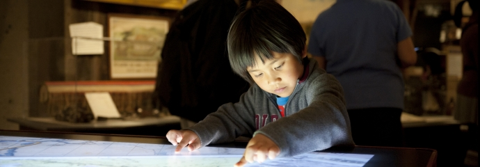 Young child using a touch screen at the Oakland Museum of California