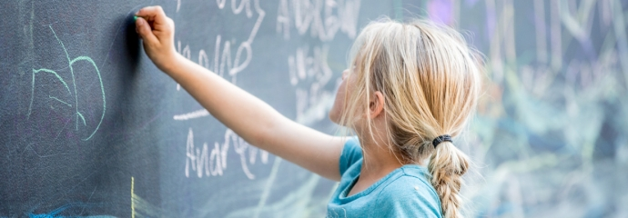 Young child drawing with chalk on a blackboard at the Oakland Museum of California