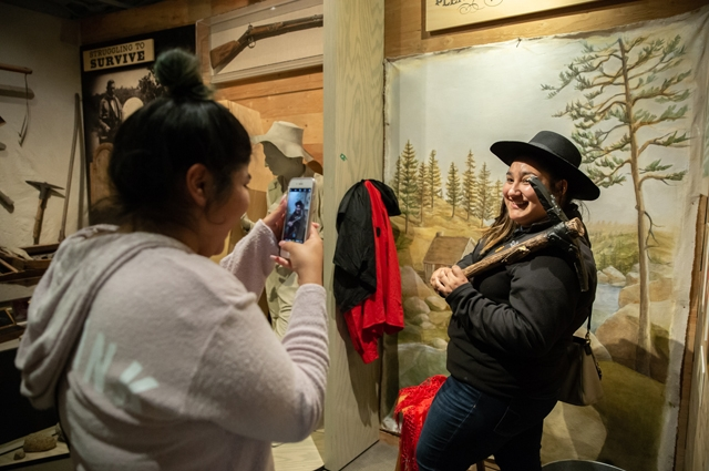 A woman takes a photo of her friend who is dressed as miner