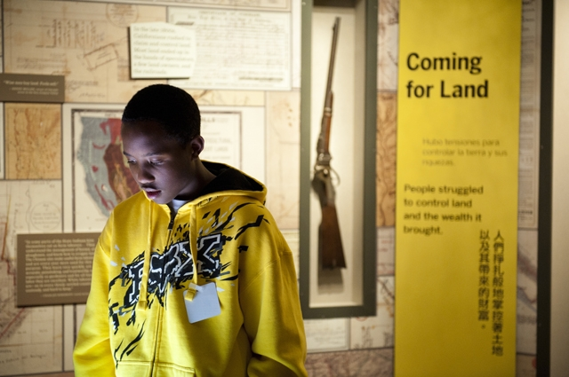 """A young boy in a yellow hoodie reads information in a section of the gallery called """"Coming for Land"""""""