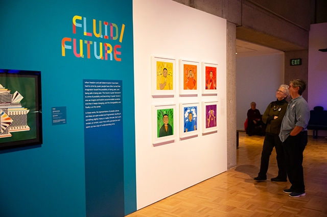Two women stand and smile at a large blue wall that reads: Fluid/Future. The wall also has 6 colorful drawn images hanging on it