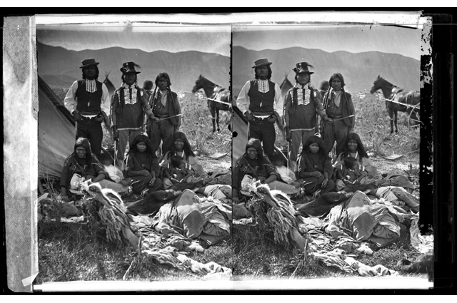 Black and white image of a group of Shoshone Indians standing in a field with a horse in the background. The image is doubled