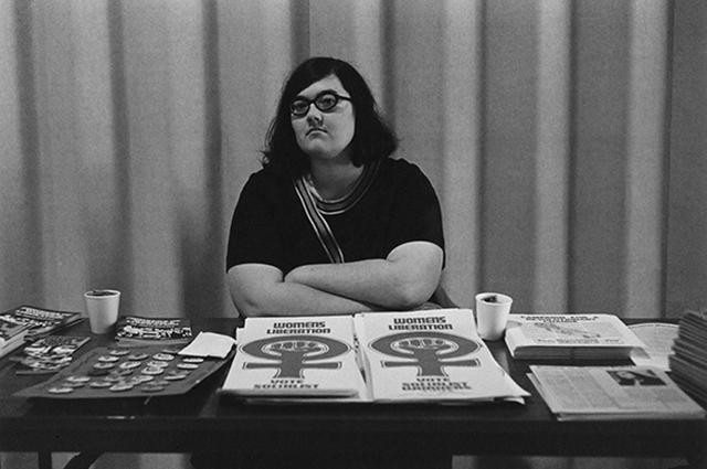 A black and white photograph of a woman with her arms crossed sitting at a table that has posters and buttons promoting Women's Liberation